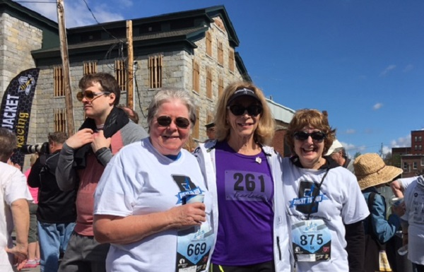NWHF Board member Dr. Judith Pipher (L) and President Jeanne Giovanninni (R) at the finish line with Kathrine Switzer